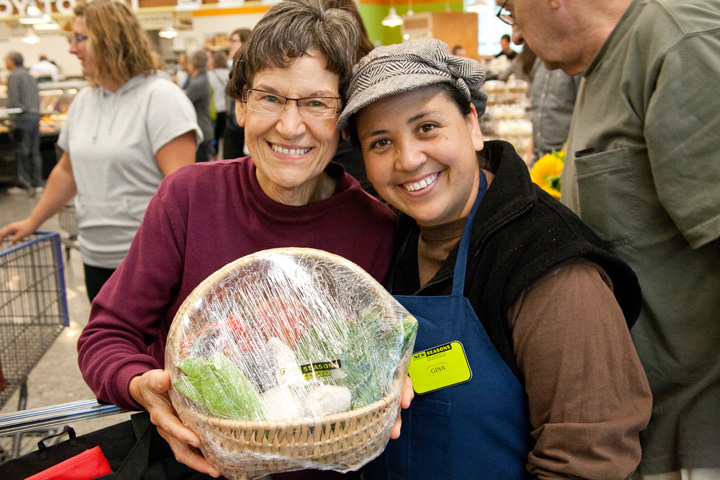 an employee with customer holding a new seasons produce basket