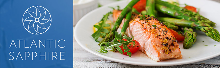 Atlantic Sapphire brand logo on left next to a plate of baked salmon with asparagus, greens and lemon.