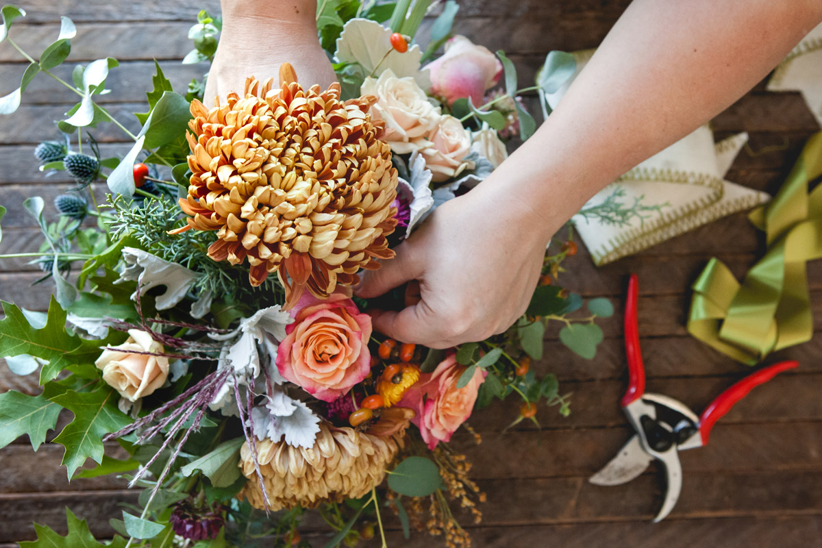 Overhead view of someone's arms assembling a floral bouquet on a wood surface surrounded by ribbon and shears