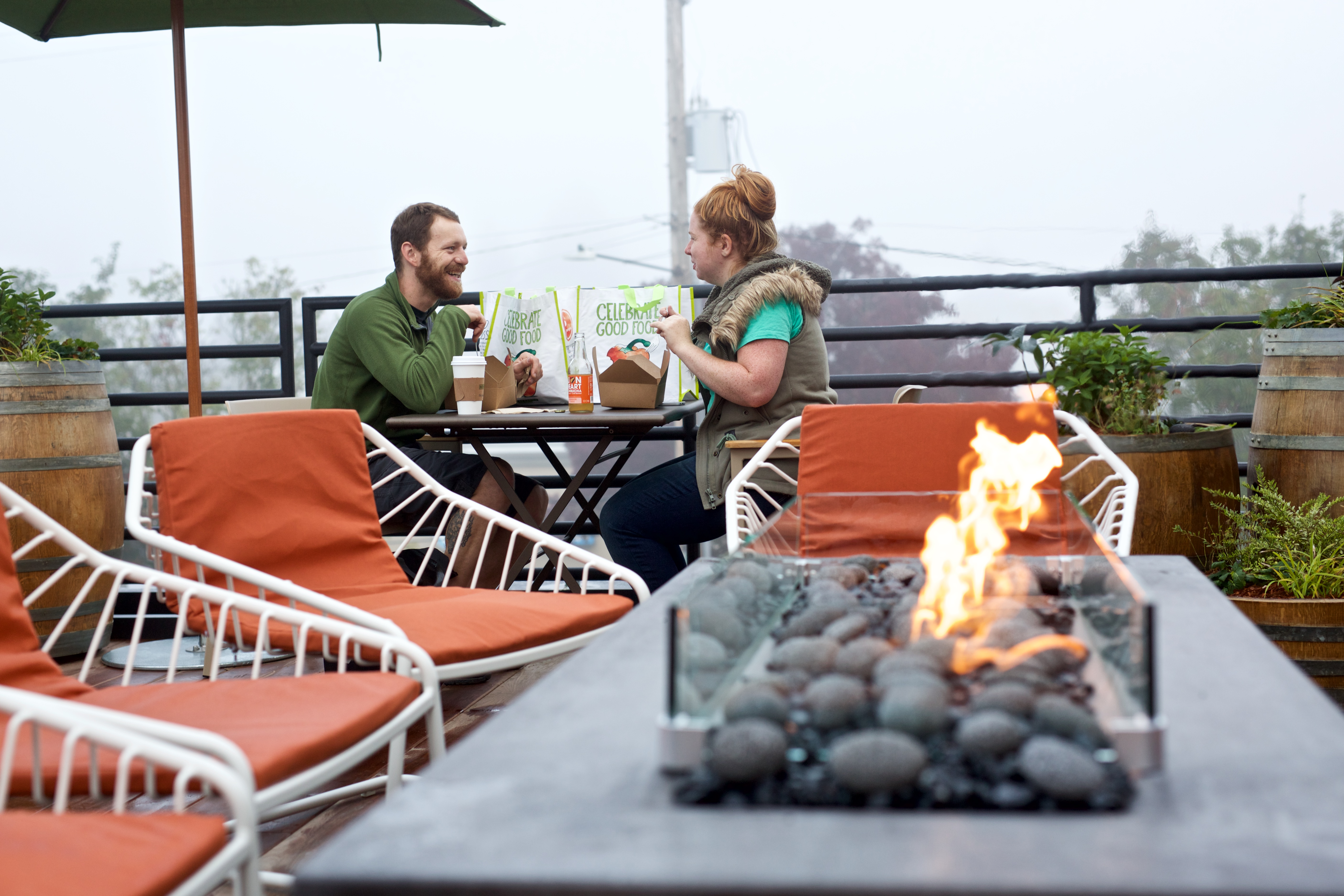 two people on a roof top with seating and a fire pit enjoying a meal from new seasons deli