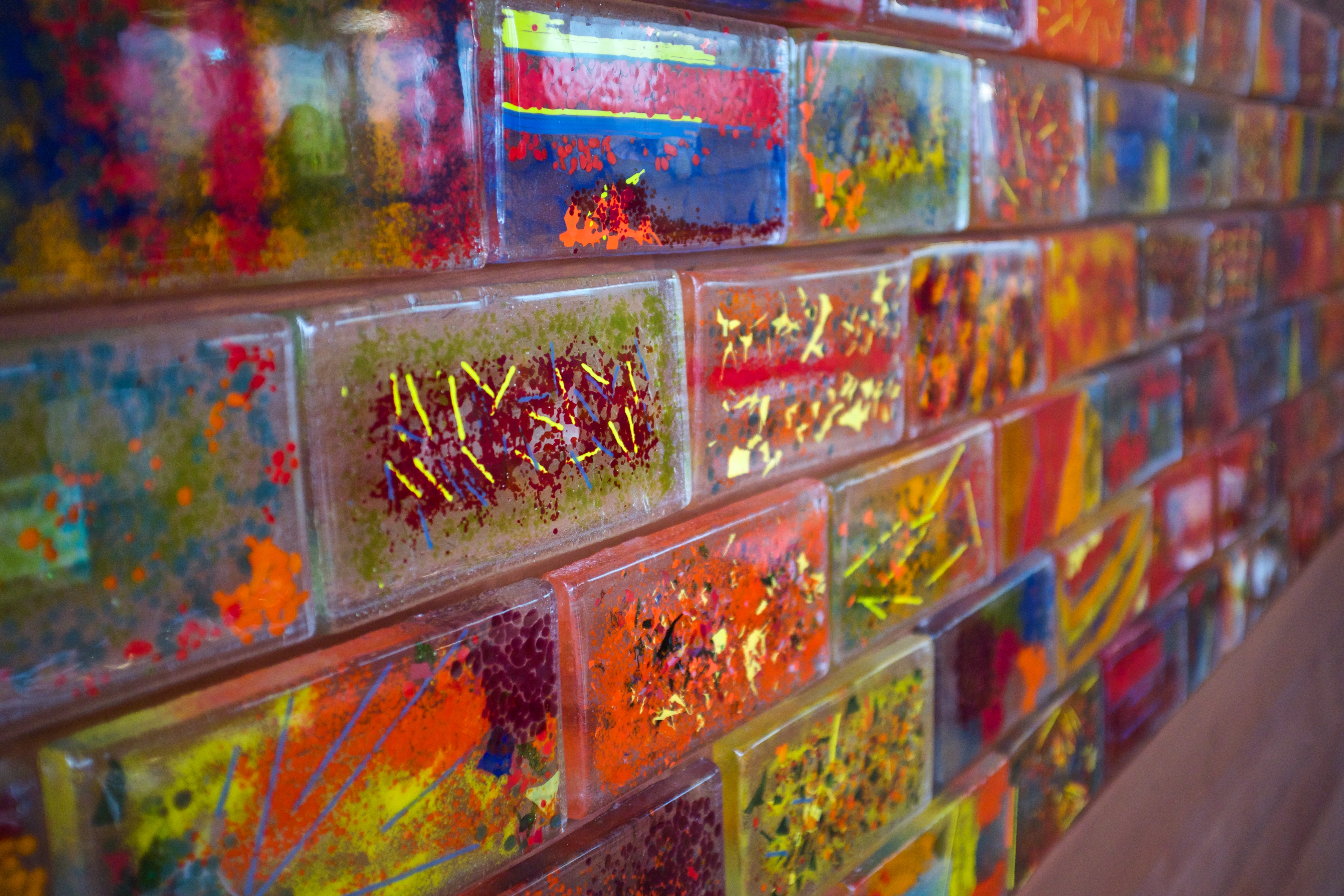 a wall of colorful and expressive glass bricks