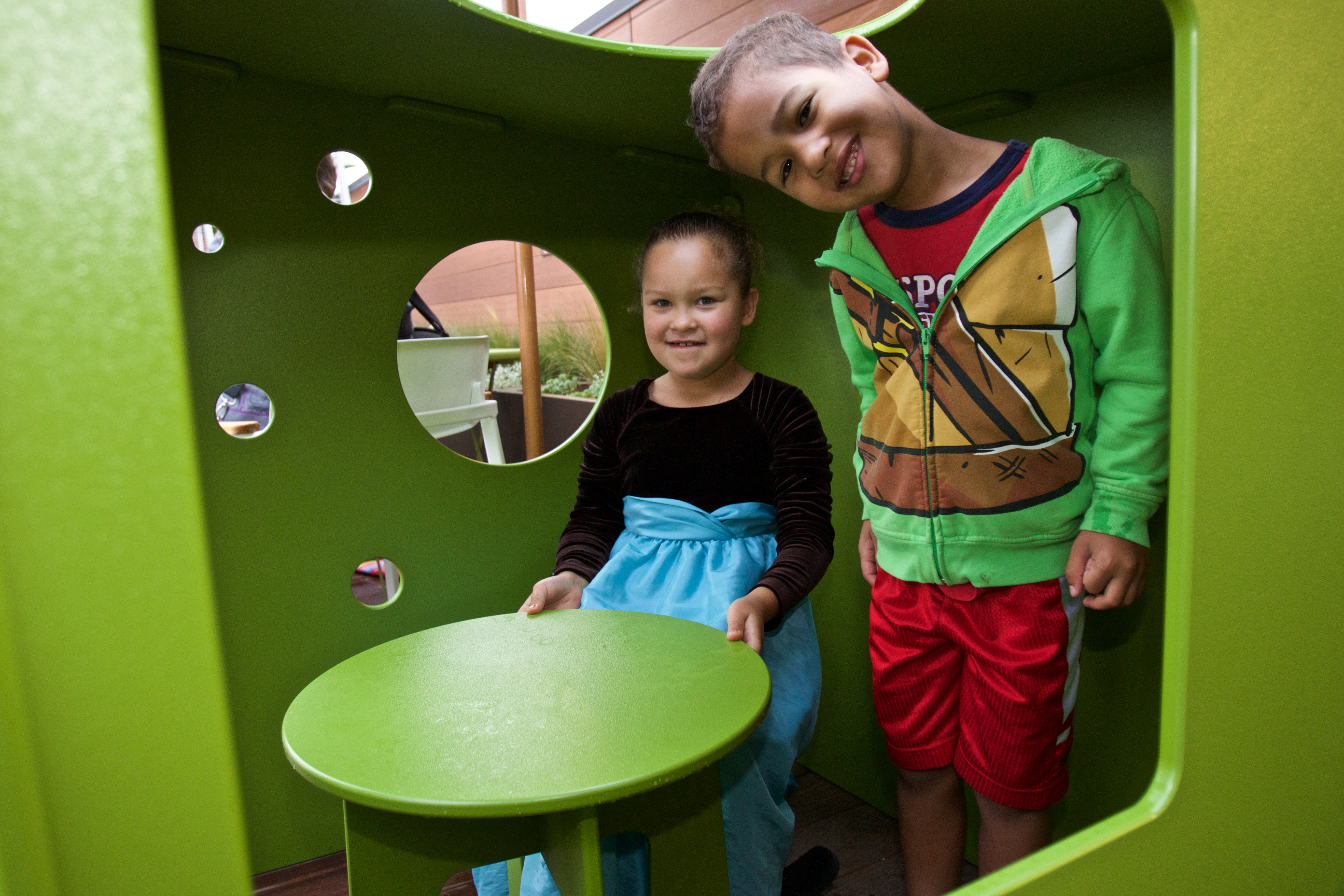 children in a bright green play box