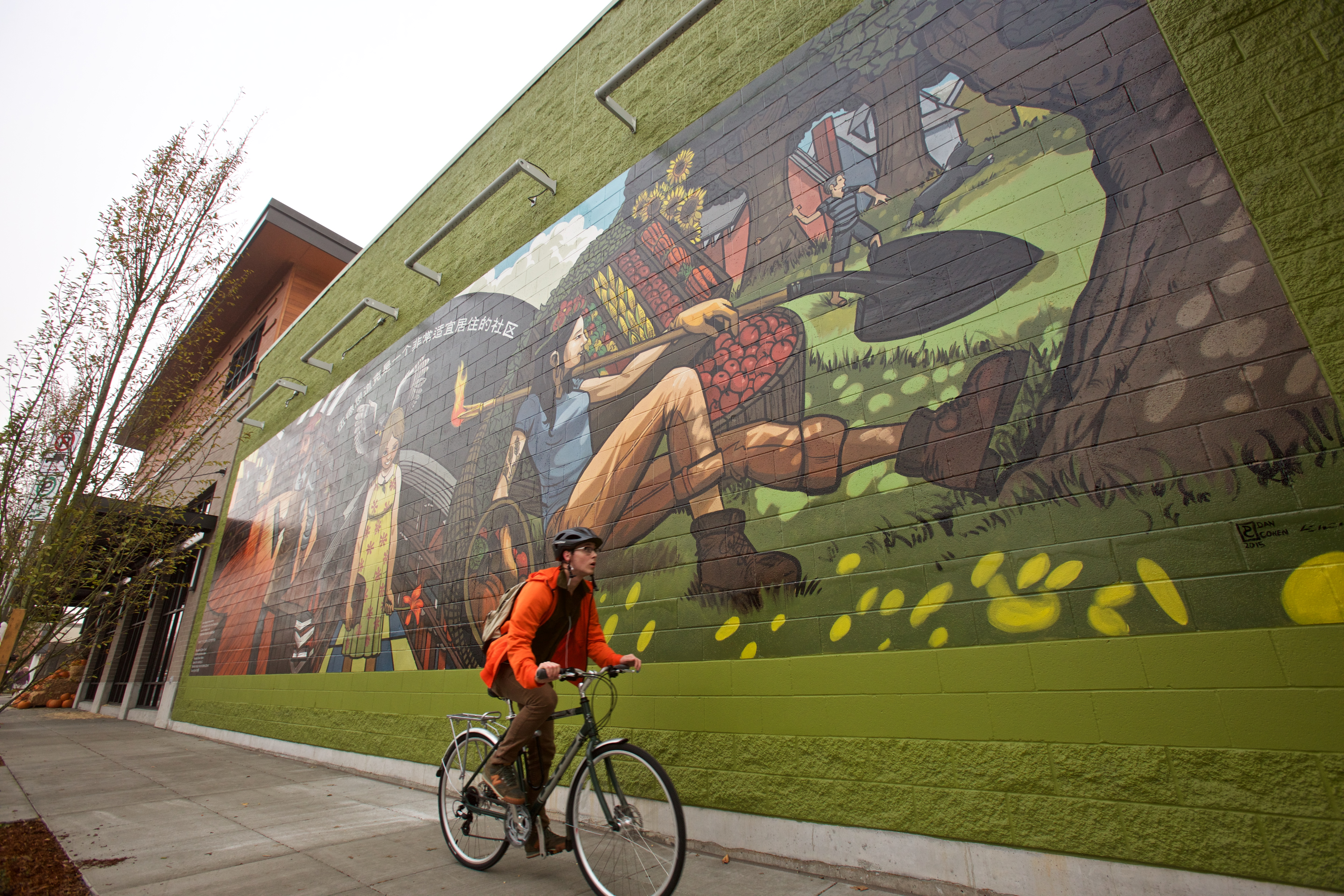 an individual biking past a new seasons building with a large colorful mural