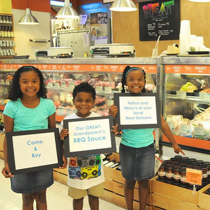 three children holding up signs promoting their grandfathers barbecue sauce available at new seasons market