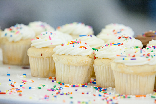 a group of vanilla cupcakes with swirled white frosting topped with rainbow sprinkles