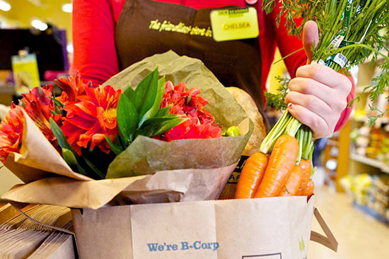 an employee bagging up flowers and produce