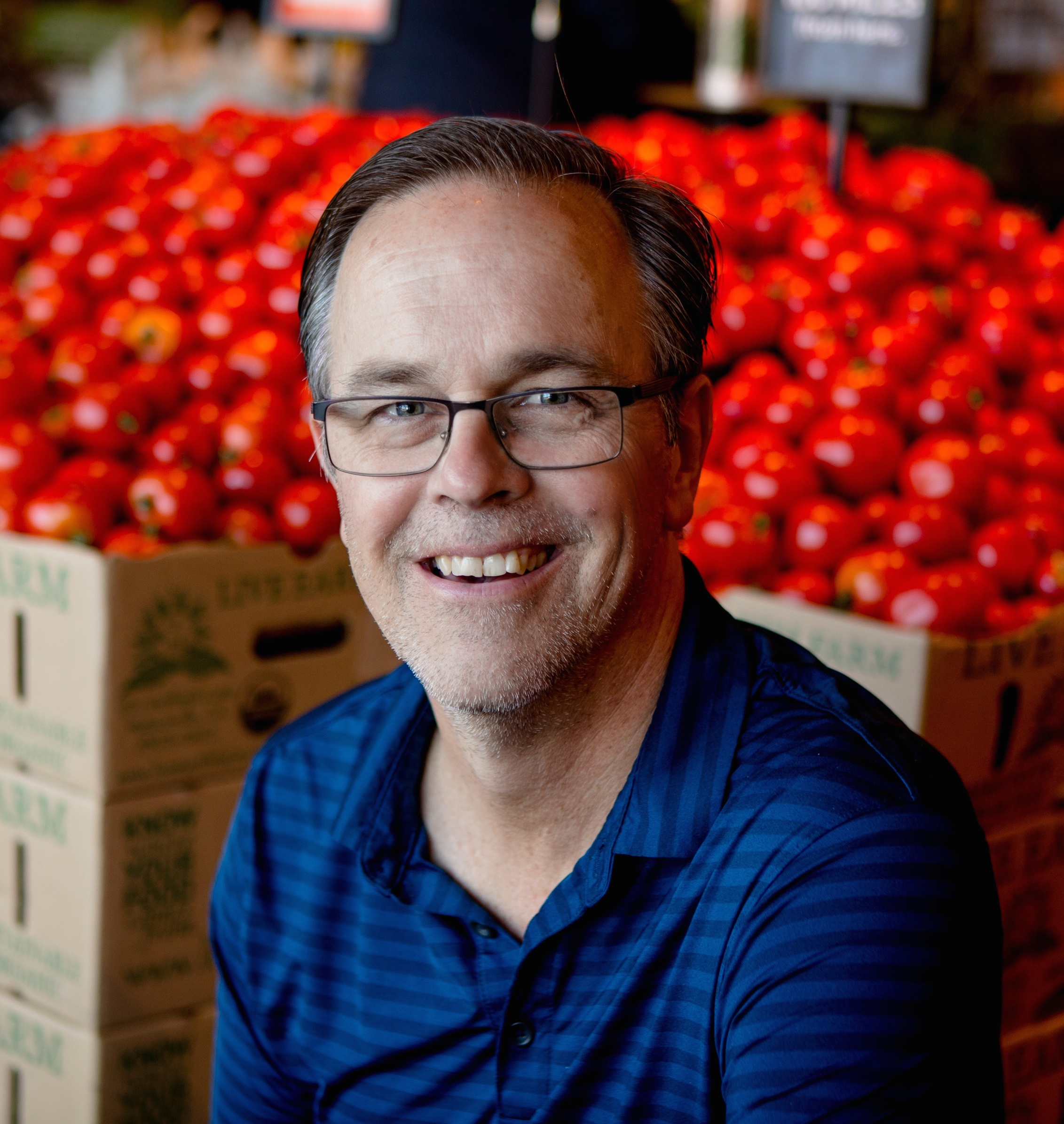 man smiling at camera in front of a pile of tomatoes