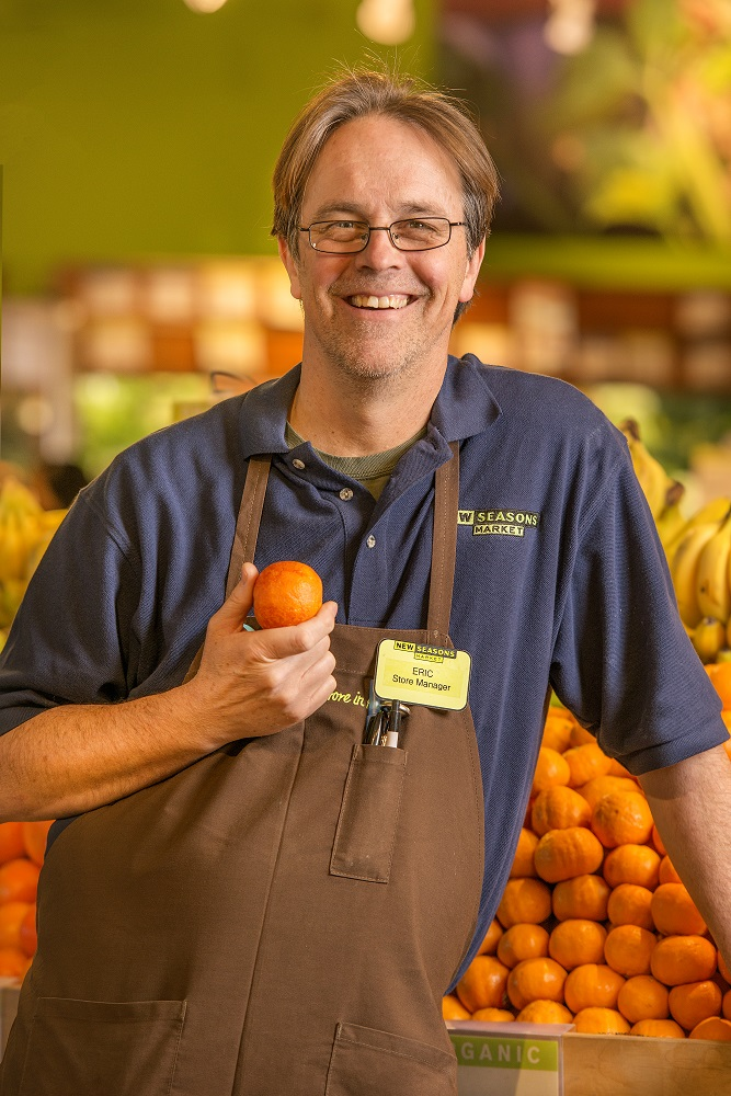 a smiling employee in the produce department holding an orange