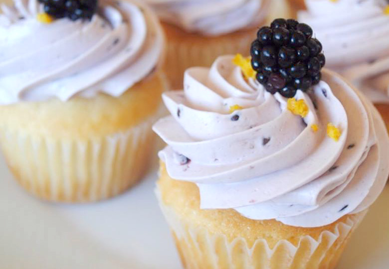 close up of a cupcakes with purple swirled frosting and a blackberry on top
