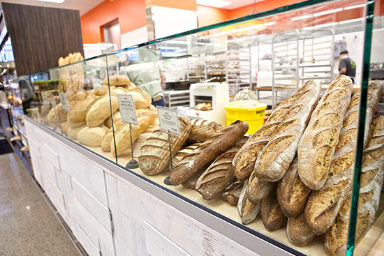 a counter top lined with all the loaves of bread in the bakery department