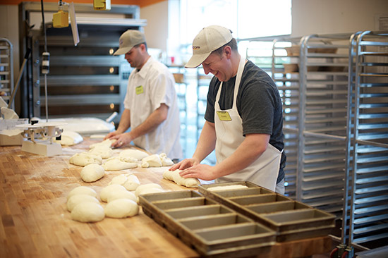 two employees kneading and shaping loaves of bread