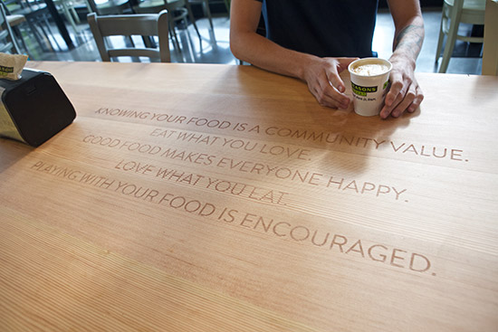 an individual picking up a hot beverage at a counter with an engraving reading knowing your food is a community value eat what you love good food makes everyone happy love what you eat playing with your food is encouraged