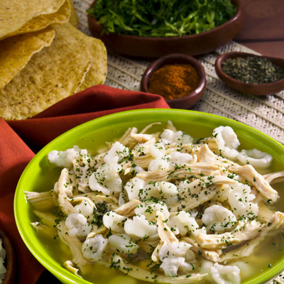 Weeknight Chicken Posole in a green bowl with side of chips and herbs