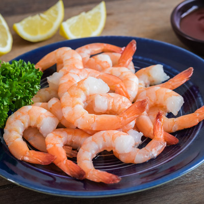 Boiled shrimp on a blue plate with lemon wedges and a side of cocktail sauce