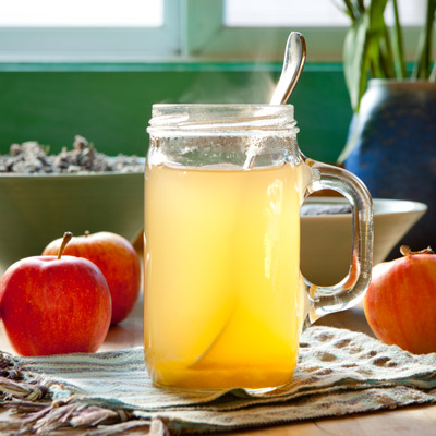 glass of hot apple cider vinegar with spoon in glass