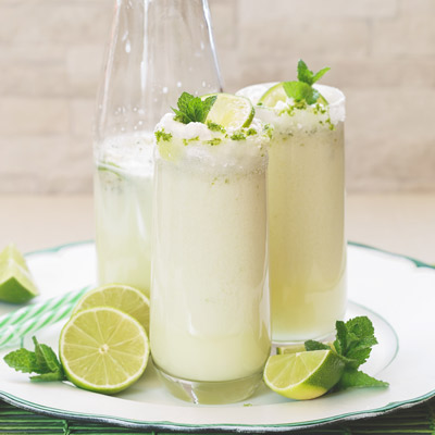 two glasses of Brazilian Lemonade with limes on a plate