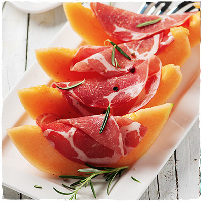Cantaloupe melon slices wrapped with proscuitto on a white plate with a rosemary garnish