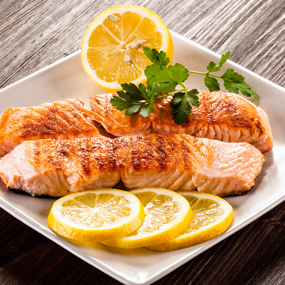 grilled salmon with lemon wedges surrounding it