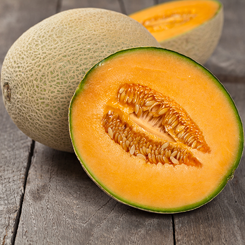 whole and half cantaloupe melons with wooden background