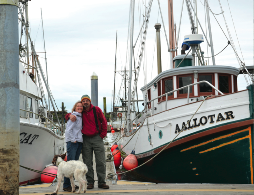 a photo of a couple and dog on a pier with boats in background