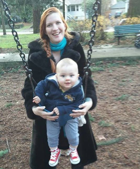mother pushing baby on swing in the park
