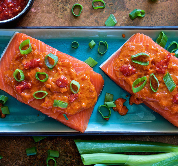 salmon with gochujang sauce and green onions on blue platter