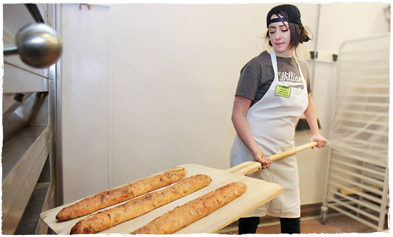 News Seasons Market employee taking out freshly baked baguettes.